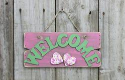 Lantligt rosa välkommet tecken med tusenskönor och hjärtor som hänger på trädörr Royaltyfri Bild
