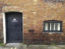 Lantligt tegelstenbyggande med dörren och fönstret royaltyfria foton