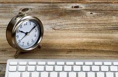 Lantligt träskrivbord med den retro klockan och tangentbordet Arkivbild