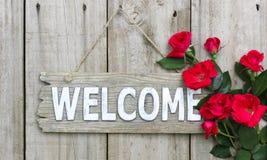 Lantligt välkommet tecken med röda blommor som hänger på den wood dörren Royaltyfri Fotografi