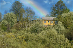 Lantligt vårlandskap med regnbågen efter en storm Arkivfoto