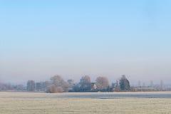 Lantligt vinterlandskap med den djupfrysta ängen Royaltyfri Foto