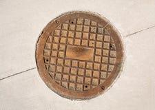 Lany żelazny manhole ląg na betonowym bruku zdjęcie stock