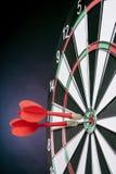 Lanza las flechas que golpean el centro de la blanco en un fondo púrpura Imágenes de archivo libres de regalías