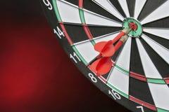 Lanza las flechas que golpean el centro de la blanco en un fondo rojo Fotografía de archivo