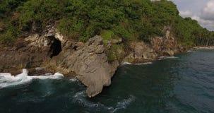 Lanzamiento aéreo de la cueva de la roca en la playa cristalina de la bahía almacen de metraje de vídeo