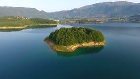 Lanzamiento aéreo de la pequeña isla en el lago Ramsko Jezero - un destino turístico del abejón cerca de Prozor, Bosnia y Herzego metrajes