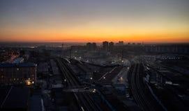 Lanzamiento a?reo de la puesta del sol sobre ciudad y de la estaci?n de tren grande con los trenes imagenes de archivo
