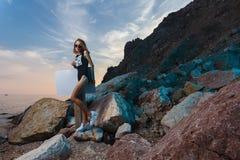 Lanzamiento adolescente de la moda de la muchacha en la playa de la puesta del sol con vacío Foto de archivo