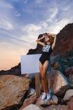 Lanzamiento adolescente de la moda de la muchacha en la playa de la puesta del sol con vacío Imagen de archivo libre de regalías