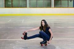 Lanzamiento adolescente de la muchacha el movimiento del patinaje sobre ruedas del pato Fotografía de archivo libre de regalías