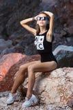 Lanzamiento adolescente joven de la moda de la muchacha en la playa de la puesta del sol Imagen de archivo