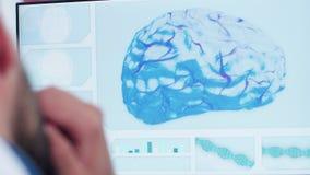 Lanzamiento ascendente cercano del doctor que mira el modelo del cerebro 3D almacen de video