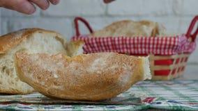 Lanzamiento cercano con un hombre que arregla el pan fresco en una cesta del pan metrajes