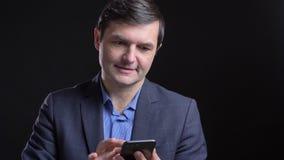 Lanzamiento de Cloesup del hombre caucásico atractivo adulto que manda un SMS en el teléfono con el fondo aislado en negro metrajes