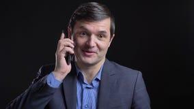 Lanzamiento de Cloesup del hombre caucásico atractivo adulto que tiene una conversación sobre el teléfono con el fondo aislado en metrajes