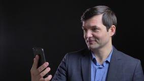 Lanzamiento de Cloesup del hombre caucásico atractivo adulto que tiene una conversación vía la llamada video en el teléfono con e almacen de metraje de vídeo