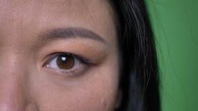 Lanzamiento de la mitad-cara del primer de la cara femenina asiática atractiva joven con los ojos que miran derecho la cámara con metrajes