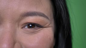 Lanzamiento de la mitad-cara del primer de la cara femenina asiática atractiva joven con los ojos que miran derecho la cámara con almacen de metraje de vídeo