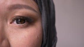 Lanzamiento de la mitad-cara del primer de la hembra musulmán atractiva adulta en hijab con el ojo que mira derecho la cámara con almacen de metraje de vídeo