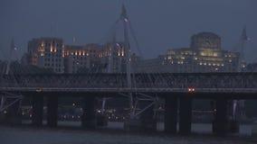 Lanzamiento de la noche con un puente metálico y suspendido en Londres sobre el río Támesis almacen de video