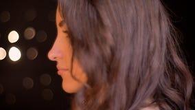Lanzamiento de la vista lateral del primer de la cara femenina caucásica atractiva joven que mira adelante con las luces del boke fotos de archivo