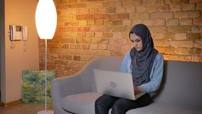 Lanzamiento de la vista lateral del primer de la hembra musulmán atractiva joven en hijab usando el ordenador portátil y del trab metrajes