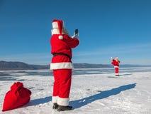 Lanzamiento de Santa Claus en un smartphone del otro Papá Noel, caminando en Foto de archivo libre de regalías