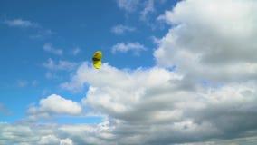 Lanzamiento de una cometa amarilla contra un cielo nublado metrajes