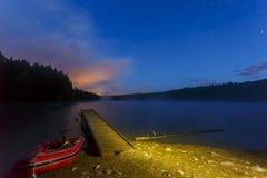 Lanzamiento del barco en un lago en la noche Imagenes de archivo