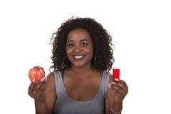 Lanzamiento del concepto sobre atención sanitaria de una mujer que elige entre una manzana y una botella de píldora Fotografía de archivo