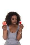 Lanzamiento del concepto sobre atención sanitaria de una mujer que elige entre una manzana y una botella de píldora Fotos de archivo