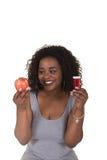Lanzamiento del concepto sobre atención sanitaria de una mujer que elige entre una manzana y una botella de píldora Imagen de archivo libre de regalías