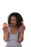 Lanzamiento del concepto sobre atención sanitaria de una mujer que elige entre una manzana y una botella de píldora Foto de archivo libre de regalías