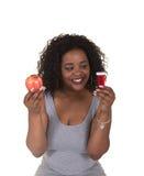 Lanzamiento del concepto sobre atención sanitaria de una mujer que elige entre una manzana y una botella de píldora Fotos de archivo libres de regalías