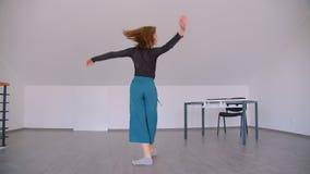 Lanzamiento del movimiento del bailarín de sexo femenino experto hermoso joven que se realiza con tolerancia en el cuarto dentro almacen de video