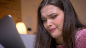 Lanzamiento del primer del adolescente femenino del caucásico moreno bonito joven que tiene una llamada video en el ordenador por almacen de video