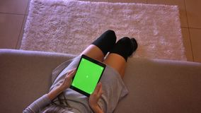Lanzamiento del primer del adolescente femenino joven que sostiene la tableta con la pantalla verde verticalmente Piernas de las  metrajes