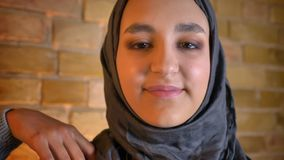 Lanzamiento del primer del adolescente femenino musulmán lindo joven en el hijab que mira derecho la cámara que sonríe feliz dent almacen de metraje de vídeo