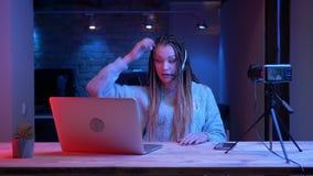 Lanzamiento del primer del blogger femenino atractivo joven con los dreadlocks en los auriculares que juegan a los videojuegos en metrajes