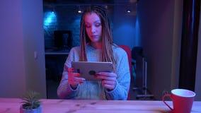 Lanzamiento del primer del blogger femenino atractivo joven con los dreadlocks que juegan el gameson video la tierra de la tablet almacen de metraje de vídeo