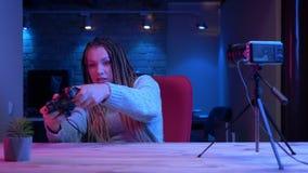 Lanzamiento del primer del blogger femenino atractivo joven con los dreadlocks que juegan a los videojuegos usando fluir de la vi almacen de metraje de vídeo