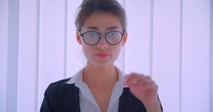 Lanzamiento del primer del businesswomanand caucásico bonito joven que fija sus vidrios y que mira la cámara que sonríe feliz almacen de video
