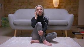 Lanzamiento del primer del caucásico atractivo joven femenino con los dreadlocks rubios que invitan al teléfono que se sienta en  almacen de video