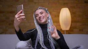 Lanzamiento del primer del caucásico atractivo joven femenino con los dreadlocks rubios que tienen una llamada video en el teléfo almacen de video