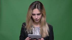 Lanzamiento del primer del caucásico atractivo joven del inconformista femenino usando la tableta con el fondo aislado en verde almacen de metraje de vídeo