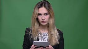 Lanzamiento del primer del caucásico atractivo joven del inconformista femenino usando la tableta y la mirada de la cámara con el almacen de metraje de vídeo