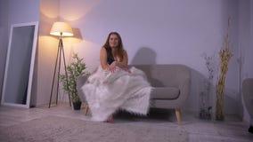 Lanzamiento del primer del caucásico bonito atractivo regordete femenino con los pechos grandes que se sientan en el sofá dentro