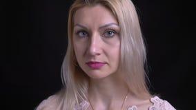 Lanzamiento del primer del caucásico envejecido midddle femenino con el pelo rubio que mira derecho la cámara con el fondo aislad metrajes