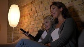 Lanzamiento del primer del caucásico joven femenino con su demostración de observación de la pequeña hija en la TV y usar un tele almacen de metraje de vídeo